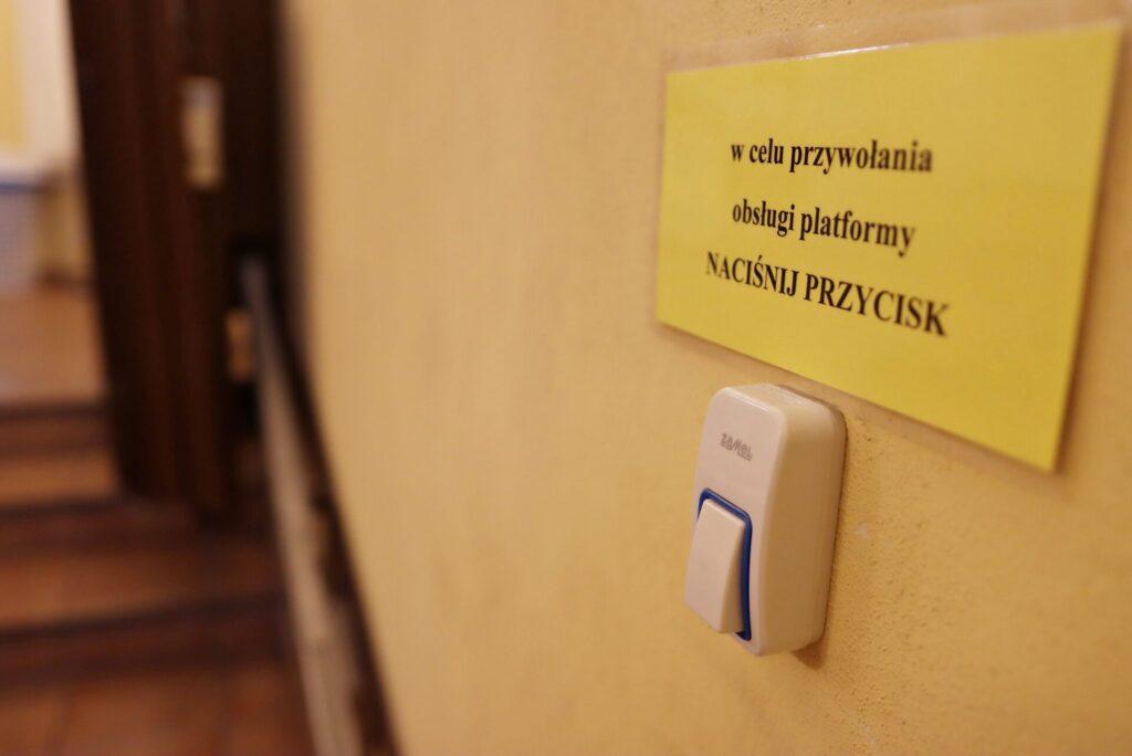Zdjęcie przedstawiające dźwig dla osób niepełnosprawnych z dzwonkiem - w celu przywołania obsługi dźwigu naciśnij przycisk