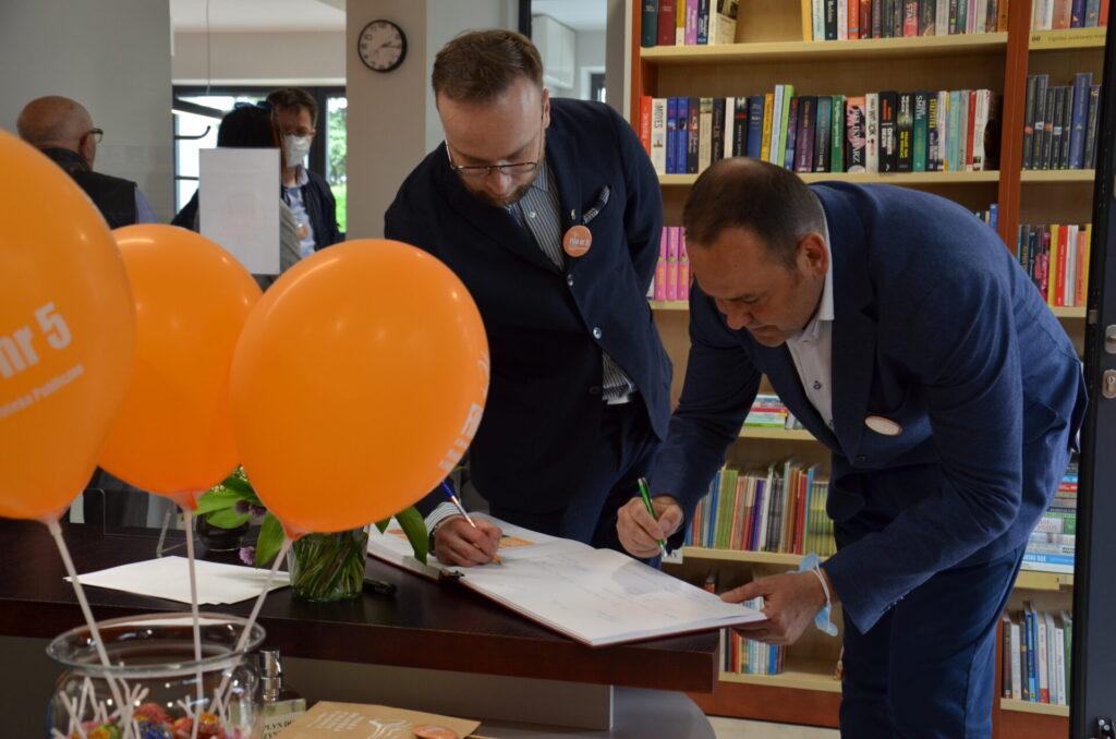 Wiceprezydent Szymon Chojnowski oraz dyrektor muzeum Dobiesław Karst wpisują się do księgi pamiątkowej