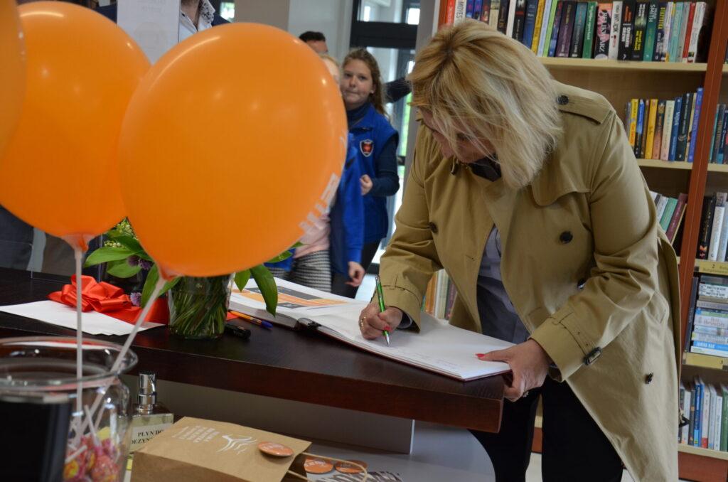 Prezydent Beata Moskal-Słaniewska wpisuje się do księgi pamiątkowej