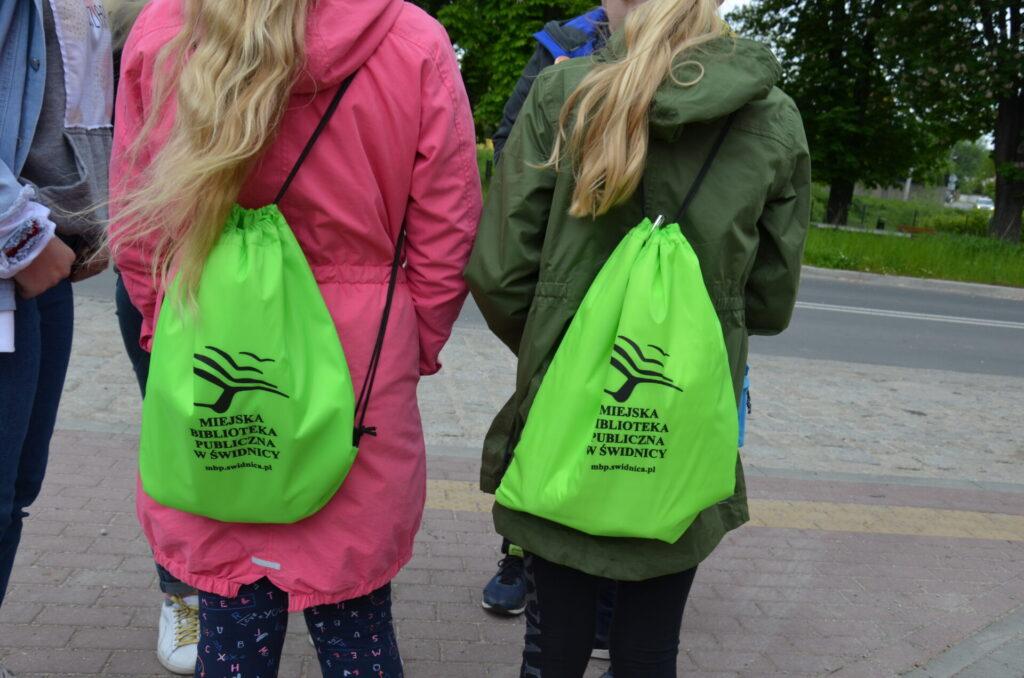 Uczestnicy gry z zielonymi plecakami z biblioteki na plecach