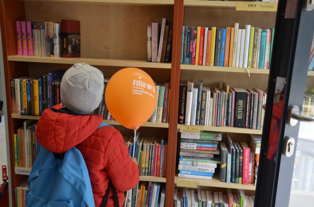 Czytelnik z pomarańczowym balonem w przestrzeni biblioteki