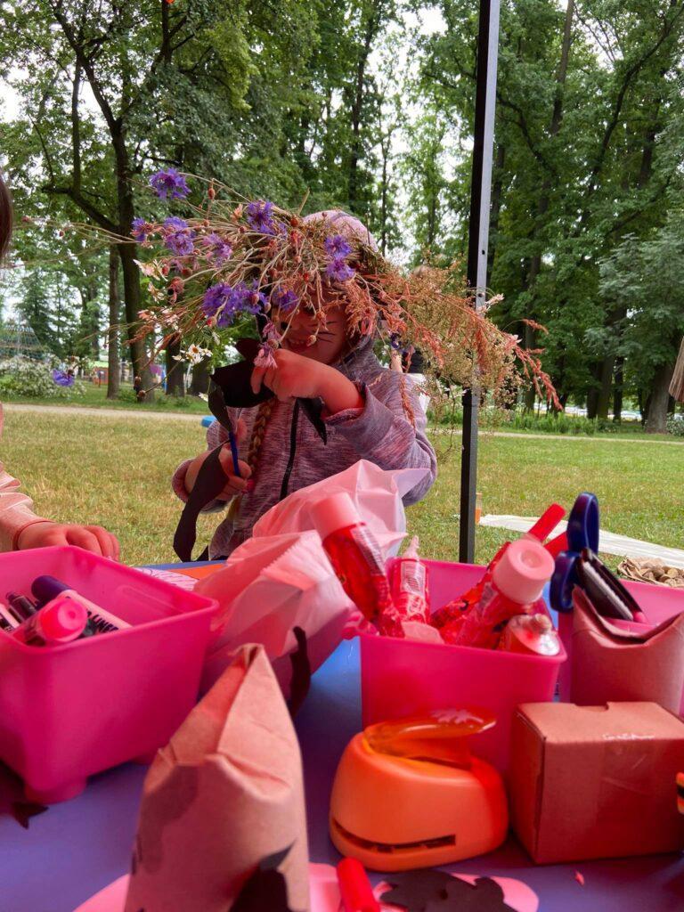 dziewczynka w trakcie wycinania z wiankiem z kwiatów na głowie