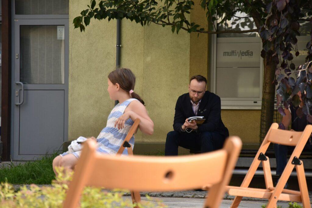 Biesiada literacka na placu z Dzikami przy bibliotece - Wiceprezydent - Szymon Chojnowski przegląda nagrodzoną książkę