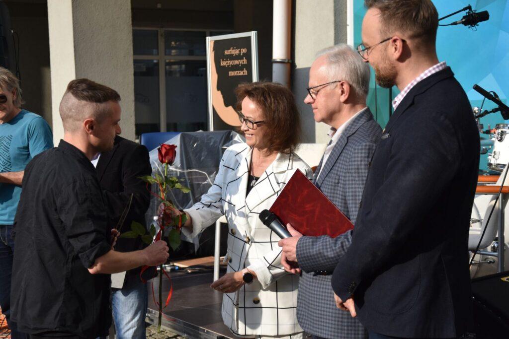 Wręczenie nagrody Mateuszowi Andale - Ewa Cuban wręcza kwiaty