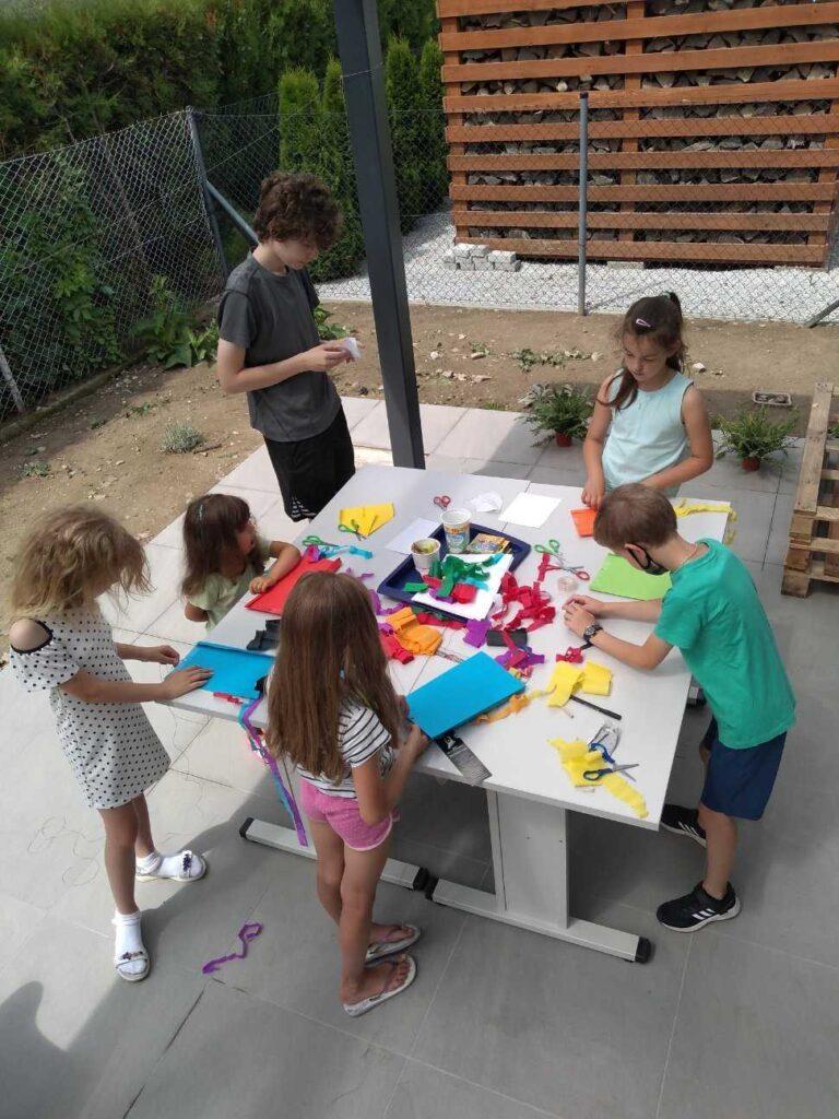 Dzieci robiące prace plastyczne na tarasie Filii nr 5