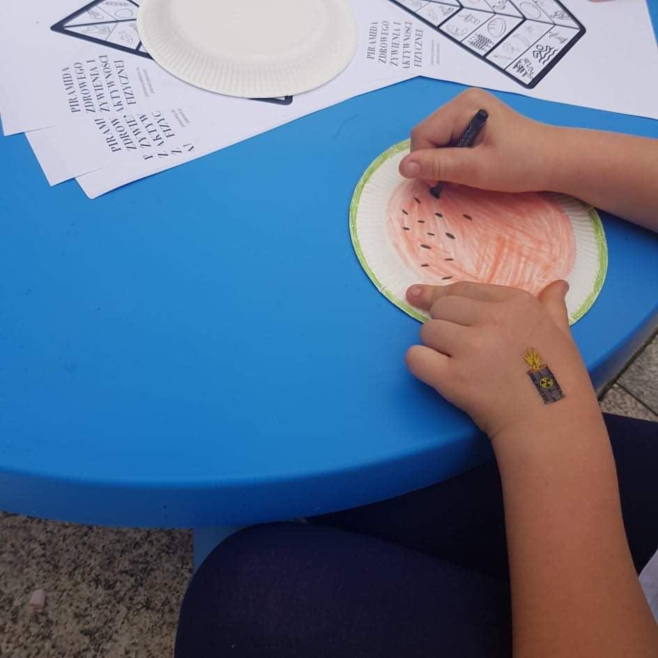 dziecko rysuje arbuza na talerzyku papierowym