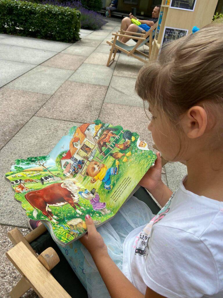 dziewczynka czyta książeczkę