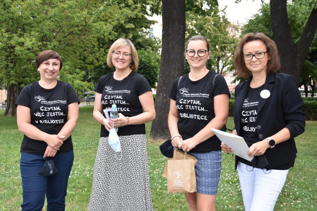 """cztery panie ubrane w czarne koszulki z napisem """"czytam więc jestem w bibliotece"""""""