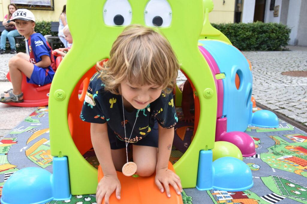 Dzieci bawią się w dużej gąsienicy
