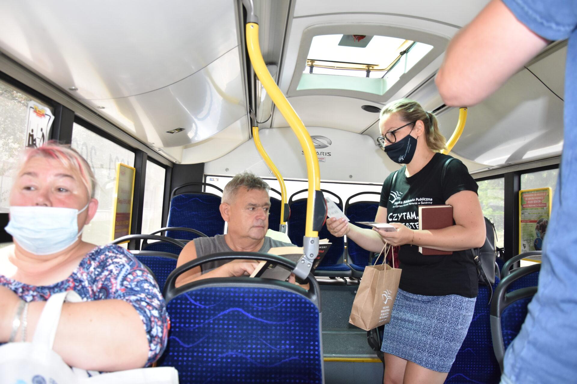 pracownik Miejskiej Biblioteki Publicznej rozdający zakładki do książek w autobusi