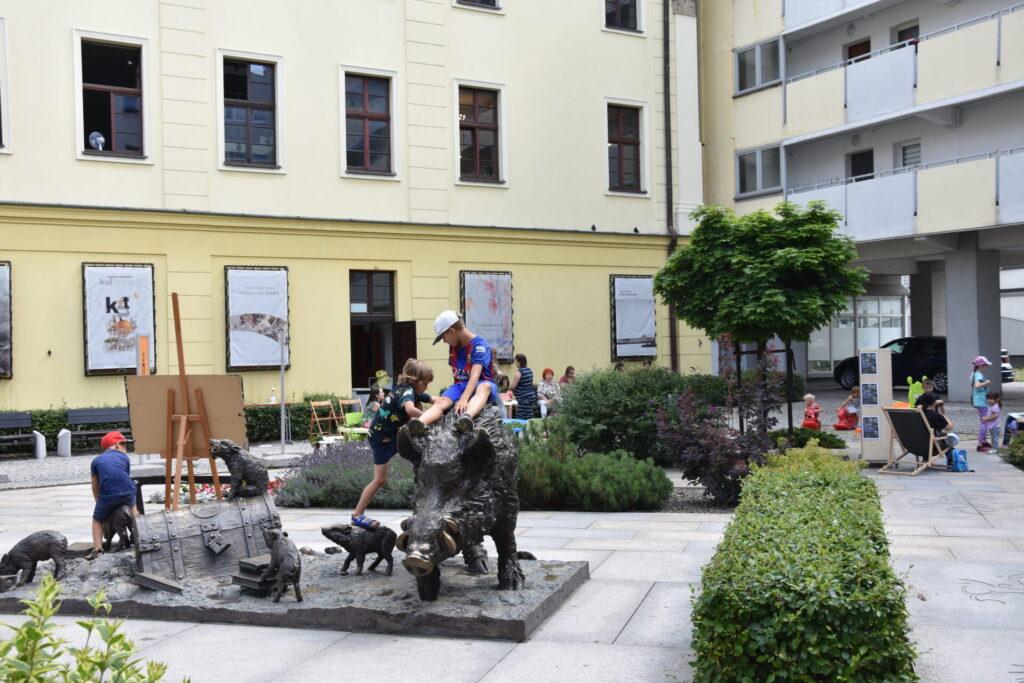 Bawiące się dzieci na rzeźbie dzików