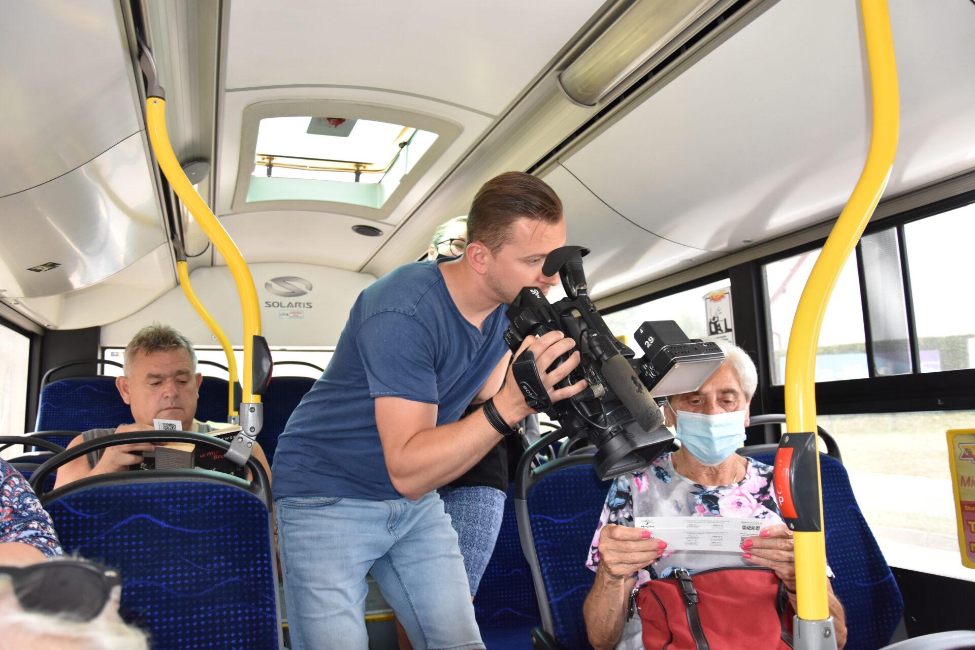 operator kamery nagrywający panią w autobusie
