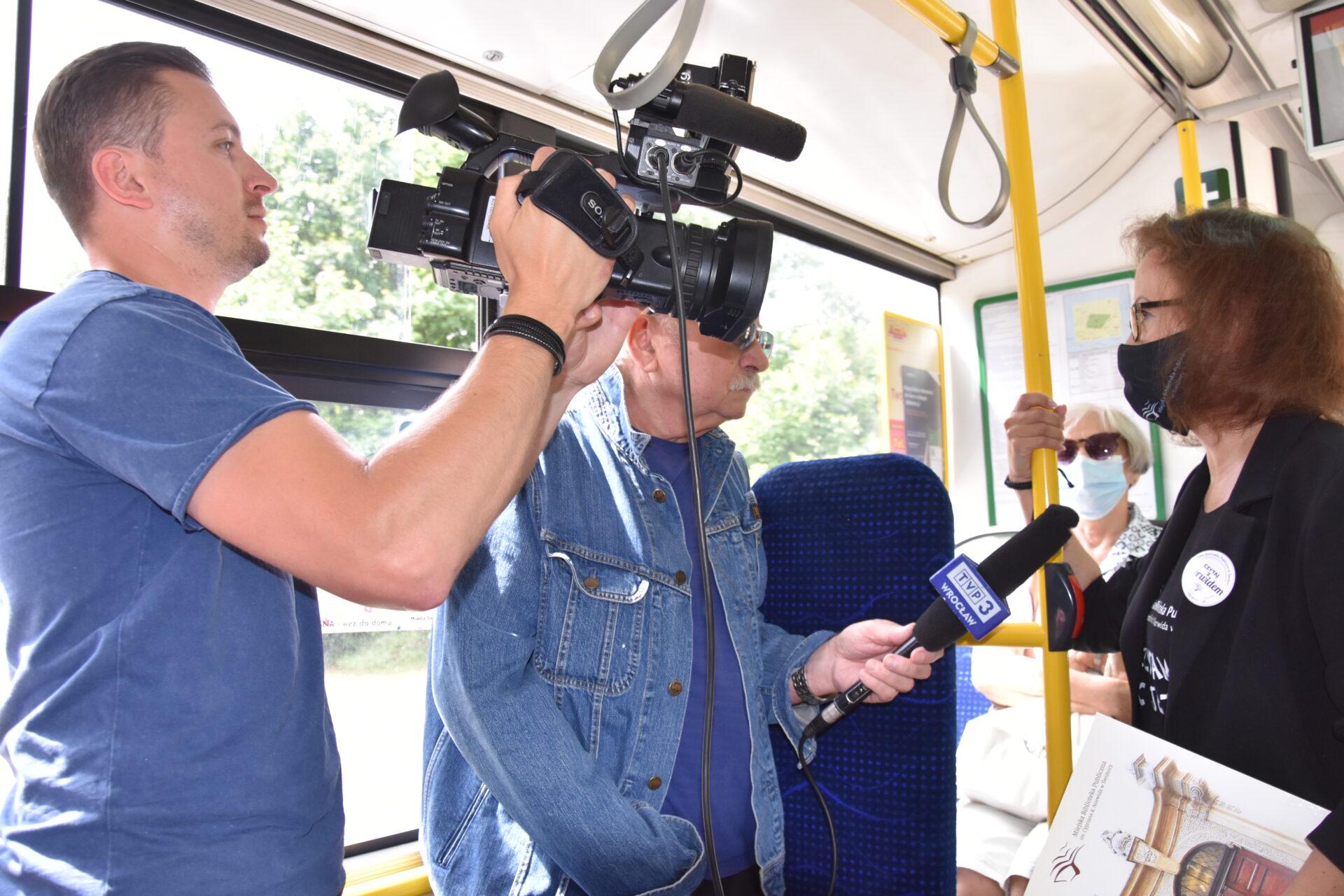 Dyrektor Miejskiej Biblioteki Publicznej udzielająca wywiadu w autobusie