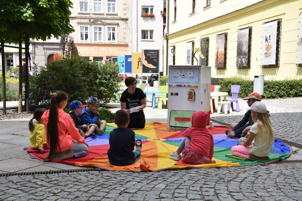 Góra bajek - spotkanie z Bajkomatem, dzieci siedzące na kolorowej chuście słuchające pani bibliotekarki