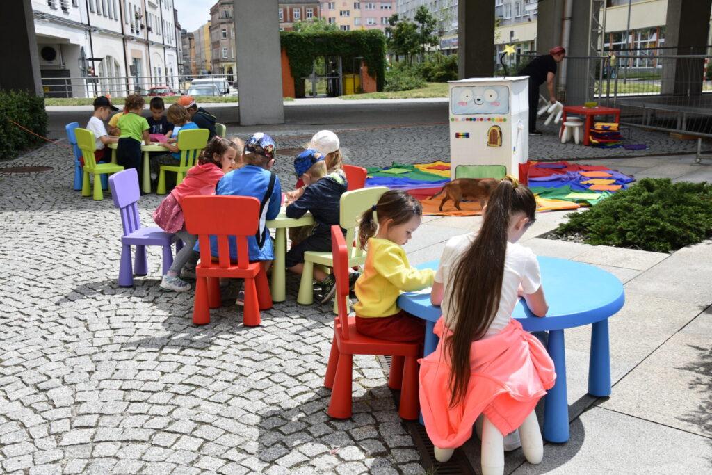 Dzieci rysujące przy kolorowych stolikach