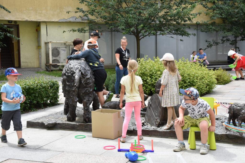 Dzieci bawiące się na skwerze z dzikami