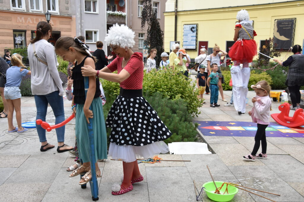 Dziewczynka uczych chodzić się na szczudłach, pomaga jej klaun