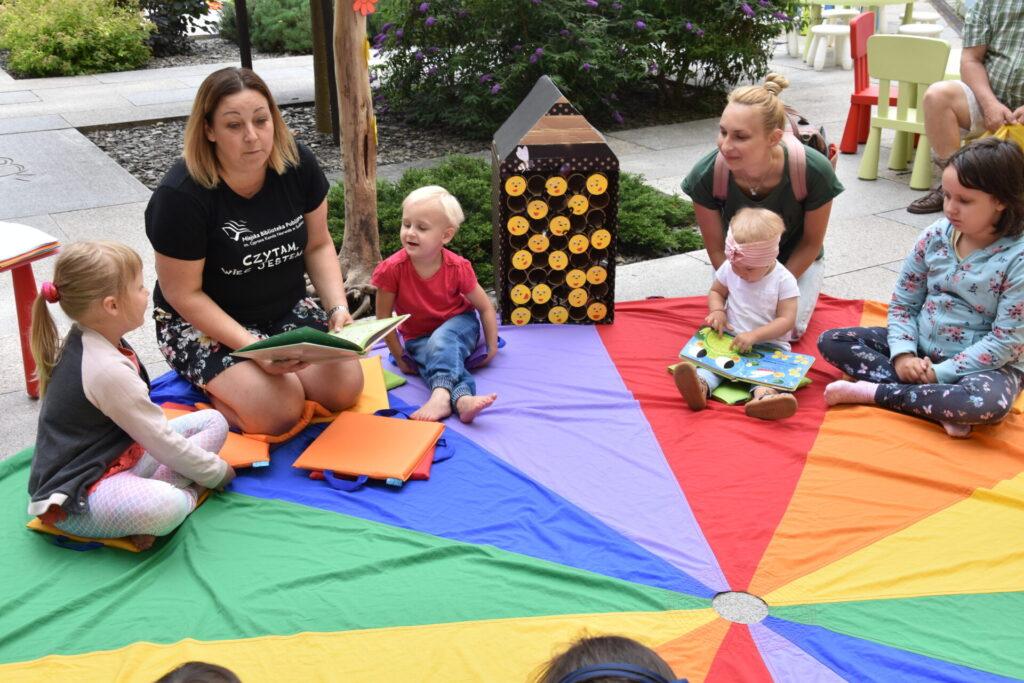 Dzieci słuchają bajki czytenej przez bibliotekarkę