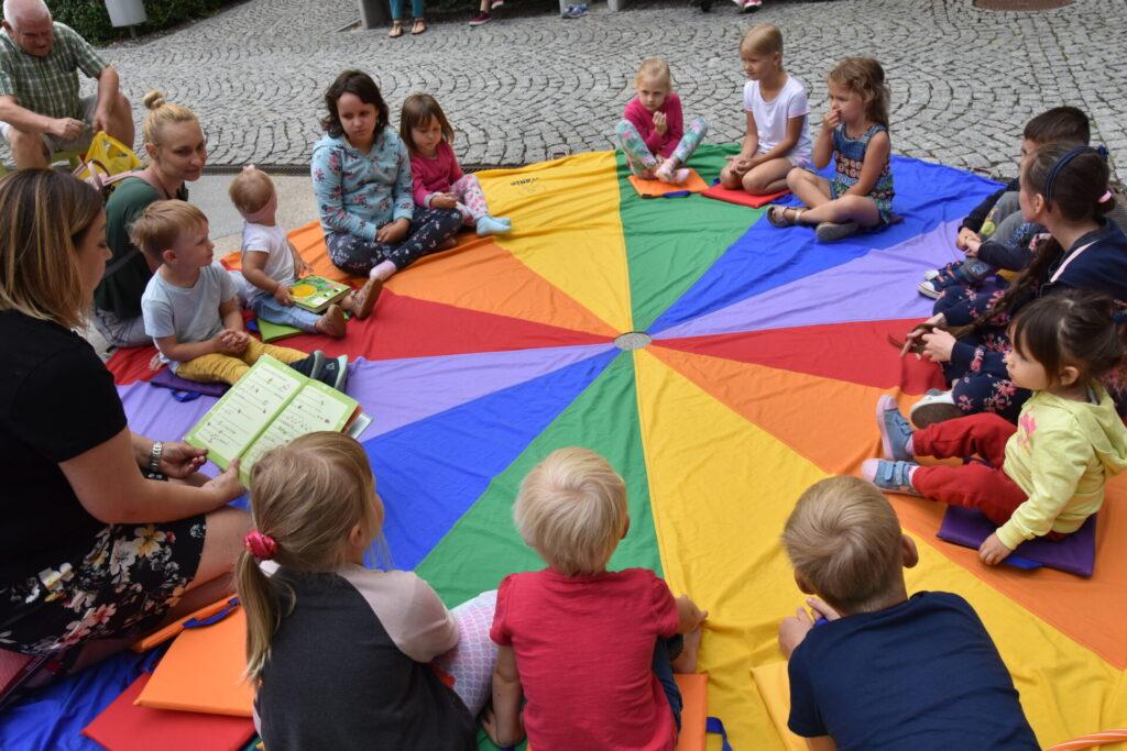 Dzieci słuchają czytanej bajki, siedzą na kolorowej chuście
