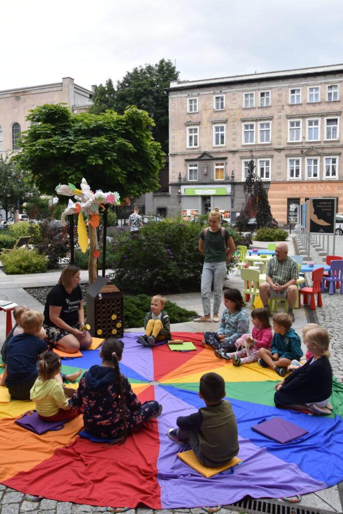 Dzieci siedzą na kolorowej chuście