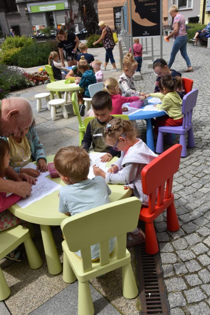 Dzieci koorują motyla przy stolikach
