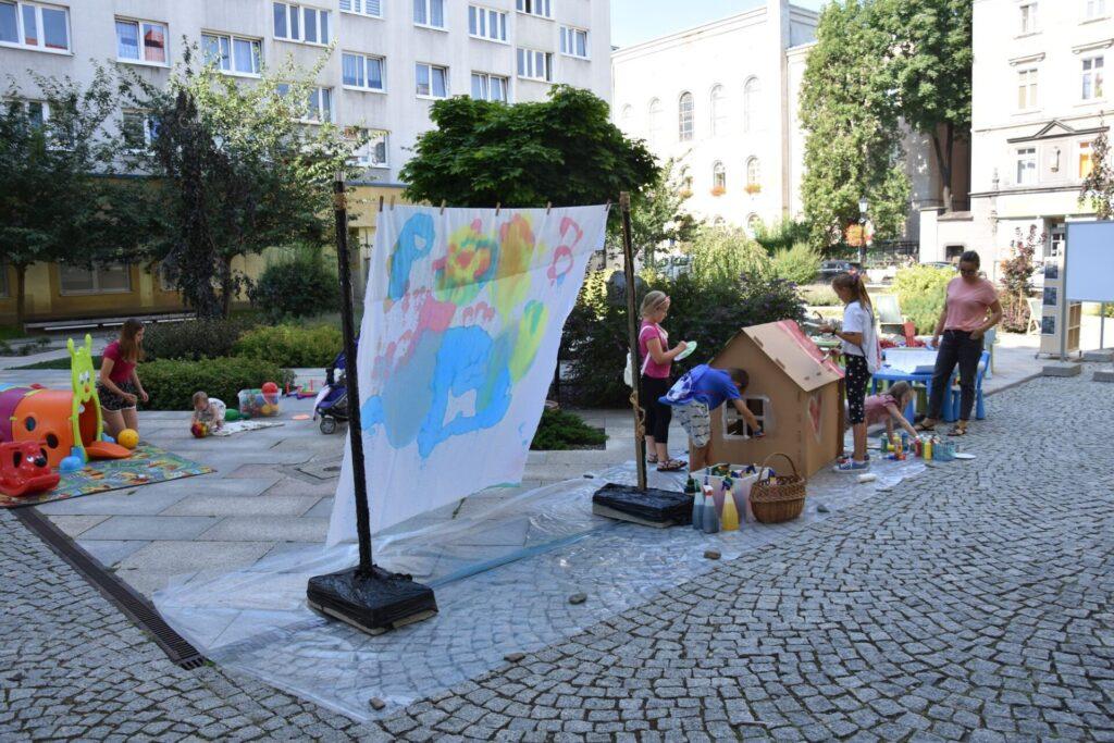 Dzieci na skwerze z dzikami malują eko farbami