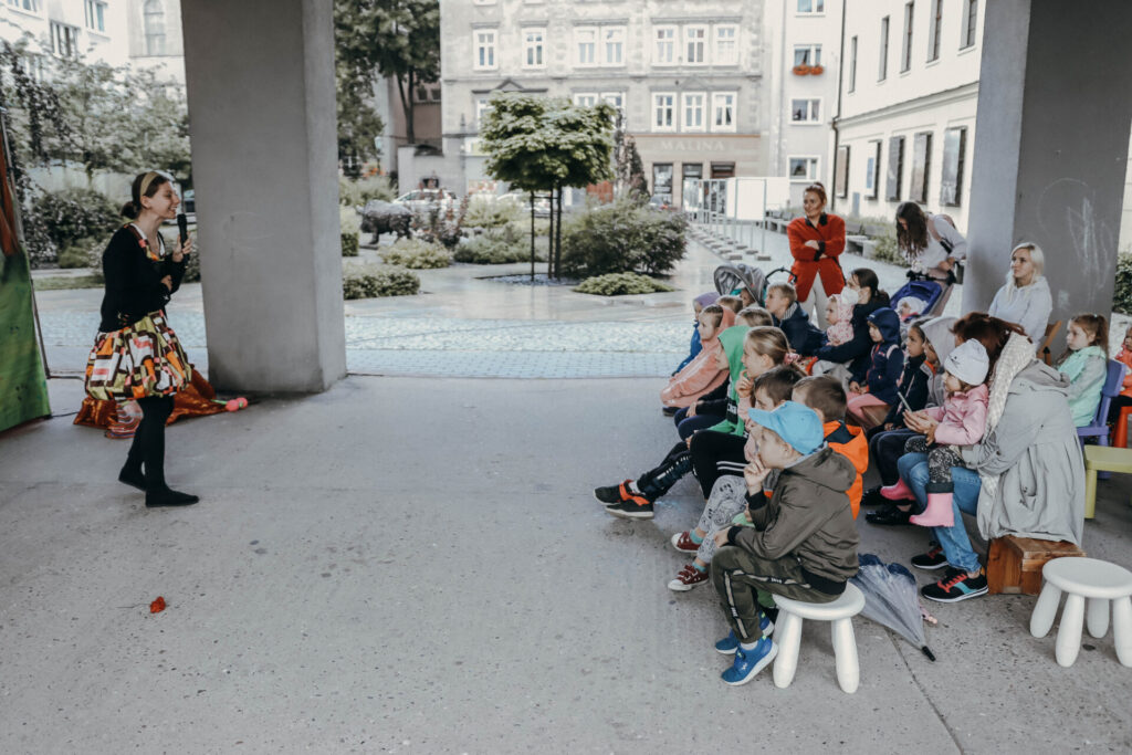 kobieta mówiąca przez mikrofon i dzieci siedzące na ławce